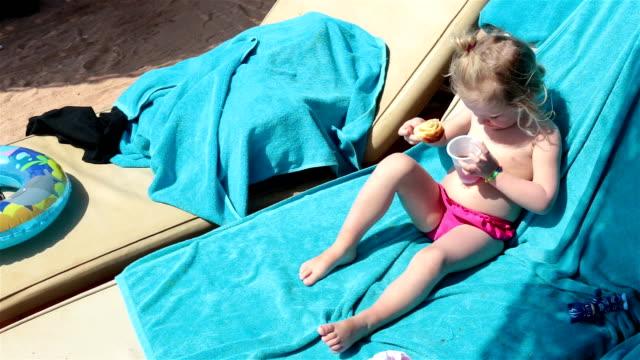 das kind liegt auf einem liegestuhl und isst croissant mit tee. - hungrig stock-videos und b-roll-filmmaterial