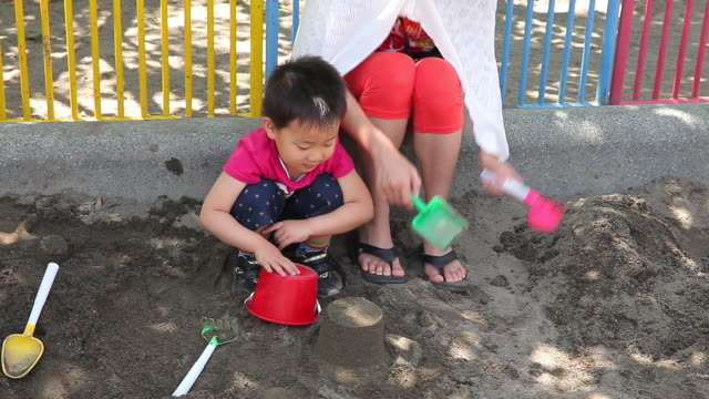 vidéos et rushes de the child who plays at a sandpit - 2 kid in a sandbox