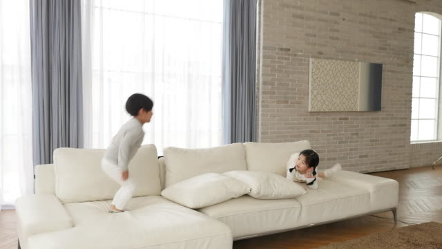 the children jump on the couch in the living room - pigtails stock videos & royalty-free footage