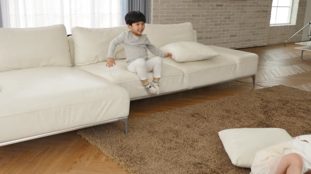 the children play on the couch in the living room - pigtails stock videos & royalty-free footage