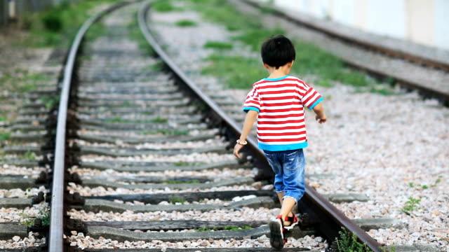 vídeos de stock, filmes e b-roll de as crianças brincam na pista - estrada de ferro