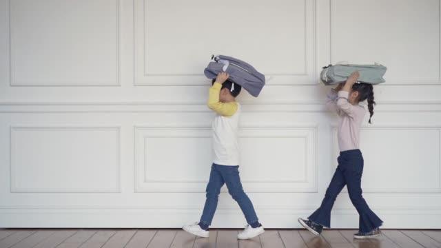 vidéos et rushes de the children walk holding a backpack in a line - vue latérale