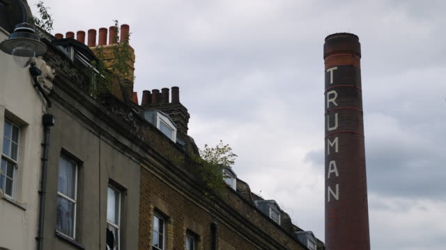 the chimney of the old truman brewery stands out against moody clouds - east london stock videos and b-roll footage