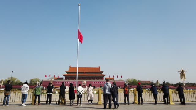 the chinese national flag flies at half-mast at the tiananmen square to mourn victims of covid-19 on april 04, 2020 in beijing, china. china will... - mourning stock videos & royalty-free footage