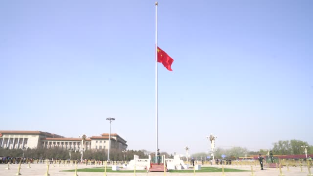 the chinese national flag flies at halfmast at the tiananmen square to mourn victims of covid19 on april 04 2020 in beijing china china will hold a... - beijing stock videos & royalty-free footage