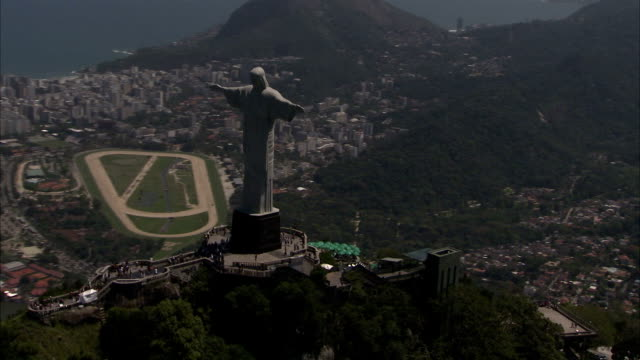 the christ the redeemer statue on top of sugar loaf mountain overlooking rio de janeiro. available in hd. - rio de janeiro stock videos and b-roll footage