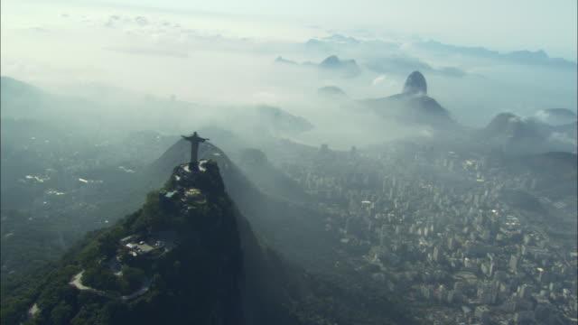 vídeos de stock, filmes e b-roll de the christ the redeemer statue overlooks fog enshrouded summits over rio de janeiro. - nevoeiro