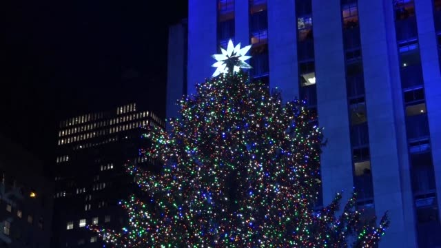 the christmas season gets underway in new york with the lighting of the rockefeller center christmas tree - illuminazione dell'albero di natale del rockefeller center video stock e b–roll