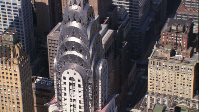 the chrysler building towers among surrounding buildings in midtown manhattan. - chrysler building stock videos & royalty-free footage