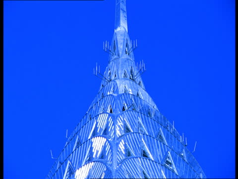 vídeos de stock e filmes b-roll de the chrysler building's spire shines like glass against the blue sky of a wintry day in new york city. - spire