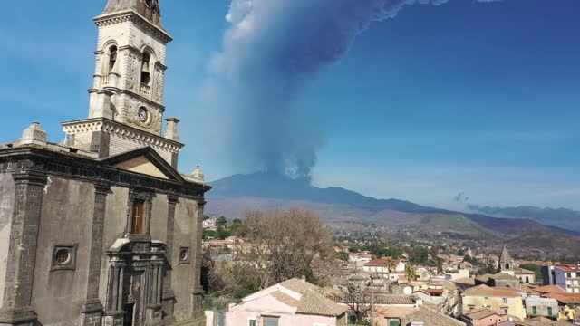 the church of san nicola in trecastagni and the eruption of mount etna with the dense smoke of ash and lapilli falling on the village on the slopes... - volcano stock videos & royalty-free footage