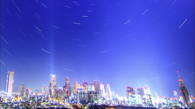 the city center; the night sky; the star trajectory: long shot; sfx; time lapse. - sternenspur stock-videos und b-roll-filmmaterial