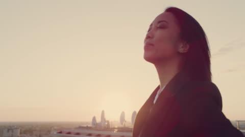 vídeos y material grabado en eventos de stock de la ciudad es mía. empresaria asiática de pie en el techo con los brazos abiertos - feminidad