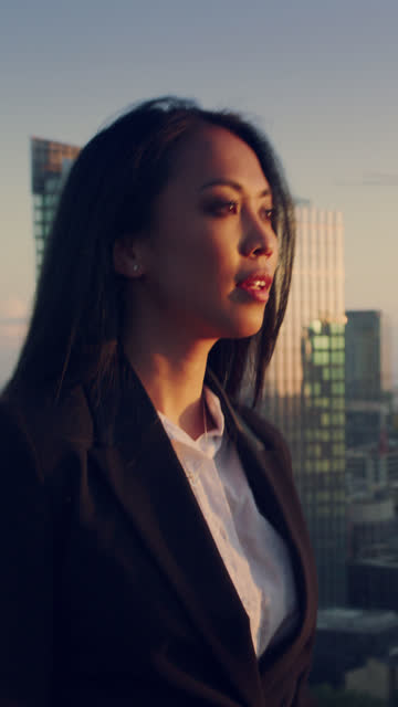 the city is mine. asian businesswoman standing on roof with open arms. vertical video - femininity photos stock videos & royalty-free footage