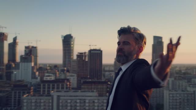 街は私のものです。屋根の上に立つビジネスマン。サンセット瞑想 - 腕を広げる点の映像素材/bロール