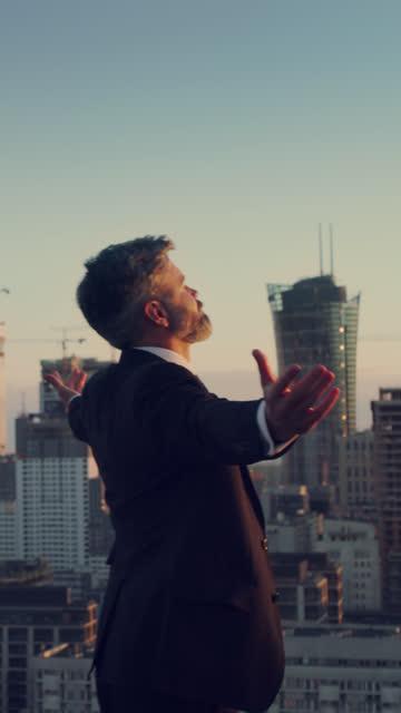 vídeos de stock, filmes e b-roll de a cidade é minha. empresário parado no telhado. meditação do pôr do sol, formato vertical - plena consciência