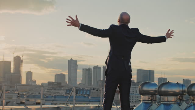 the city is mine. businessman standing on roof with open arms - alla moda video stock e b–roll