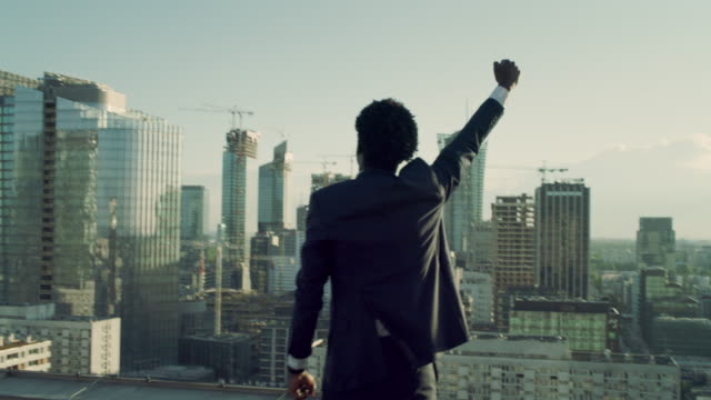 the city is mine. businessman standing on roof with winning gesture - satisfaction stock videos & royalty-free footage