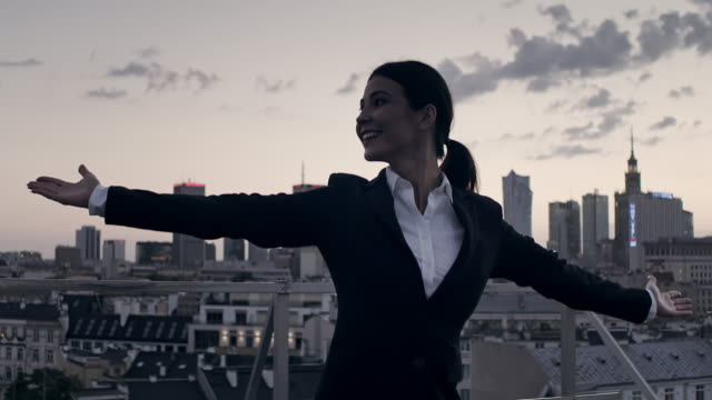 vídeos de stock e filmes b-roll de the city is mine. businesswoman standing on roof with open arms - satisfação