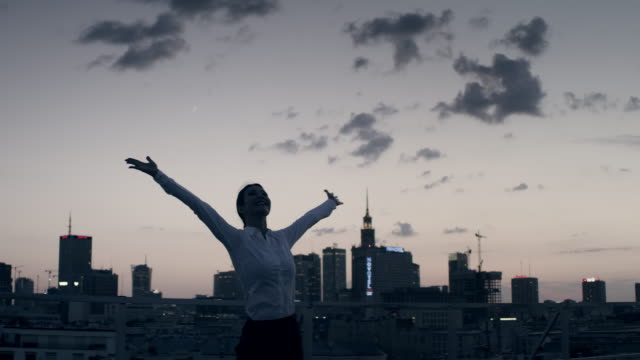the city is mine. businesswoman standing on roof with open arms - arms outstretched stock videos & royalty-free footage