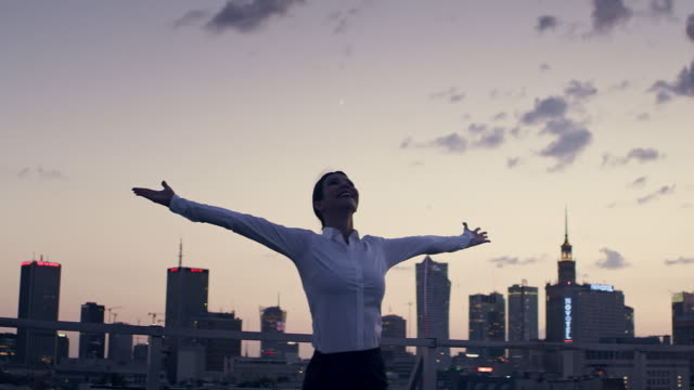 the city is mine. businesswoman standing on roof with open arms - joy stock videos & royalty-free footage