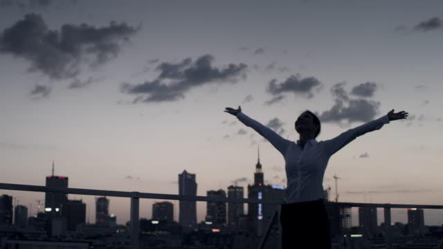 vídeos de stock, filmes e b-roll de a cidade é minha. mulher de negócios que está no telhado com braços abertos - telhado