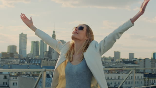 the city is mine. businesswoman standing on roof with open arms - turning stock videos & royalty-free footage