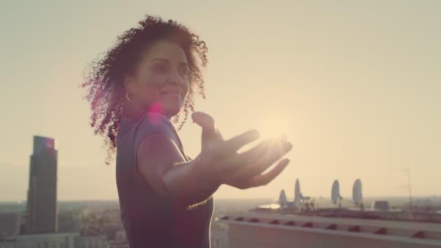 vidéos et rushes de la ville est à moi. femme d'affaires de race mélangée restant sur le toit avec les bras ouverts - satisfaction