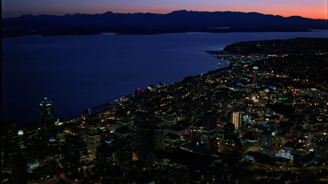The city lights of Seattle, Washington illuminate Puget Sound.