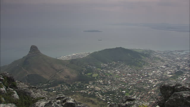 the city of cape town, south africa, spreads out between lion's head mountain and the ocean. - lion's head mountain stock videos and b-roll footage