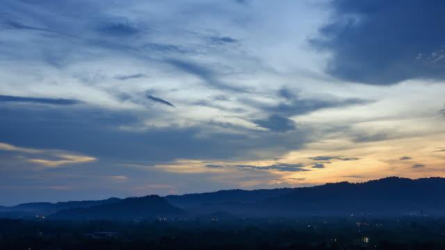 vídeos de stock, filmes e b-roll de 4k tempo lapso noite para dia (4096 x 2160): a noite de paisagem urbana de dia, beautiful cloudscape com nuvens grandes, construção e nascer do sol rompendo nuvem em massa. (apple prores. 422(hq)). - time lapse da noite para o dia