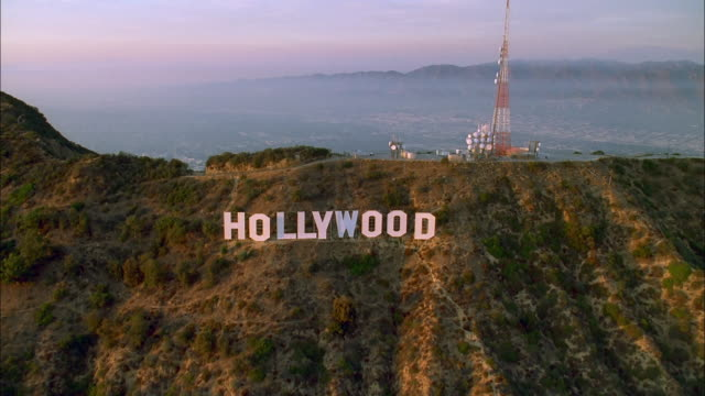 The classic Hollywood sign sits on a wooded hillside above Hollywood, California. Available in HD.