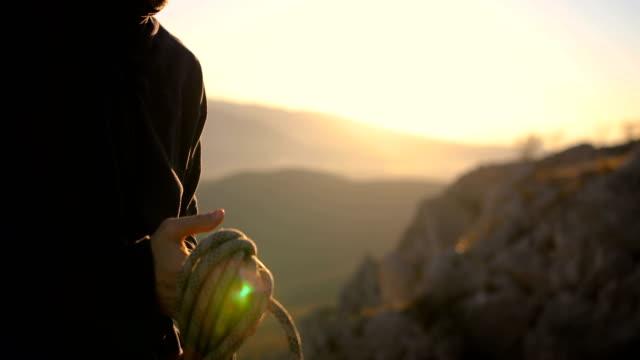 klättrare coil ett rep för att lägga den i ryggsäcken när det inte behövs - klätterutrustning bildbanksvideor och videomaterial från bakom kulisserna