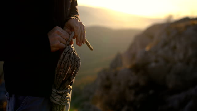 the climber coil a rope to put it in the backpack when it is not needed - climbing equipment stock videos & royalty-free footage