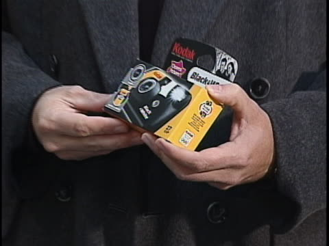 the clip is silent. shot is a close up of a man holding a disposable black and white camera and the shot slowly zooms out to a medium close up.... - 使い捨てカメラ点の映像素材/bロール