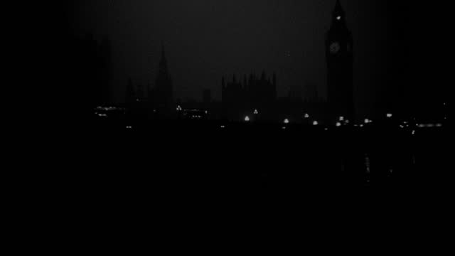 the clock face of big ben glows behind westminster bridge on a foggy night in london. - clock tower stock videos & royalty-free footage