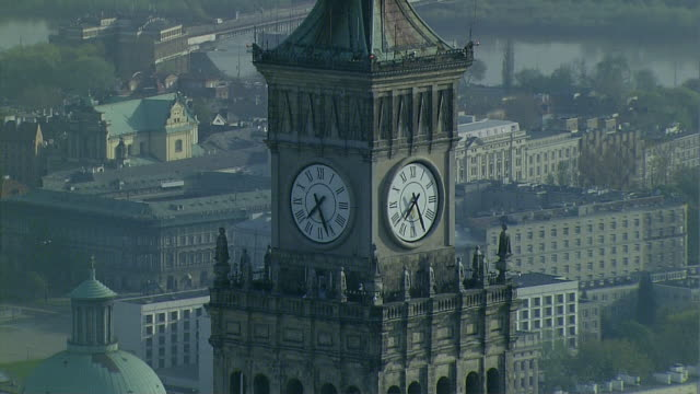 the clock on the tower of the palace of culture and science in warsaw. a panorama of the centre and a view of the vistula river and its right bank. - palace stock-videos und b-roll-filmmaterial