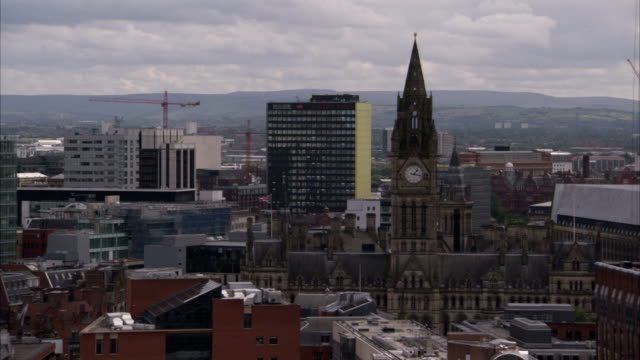 The clock tower of Manchester's Town Hall towers above modern skyscrapers. Available in HD.