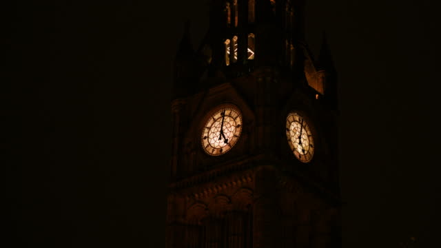 the clock tower of the manchester town hall is illuminated at night - town hall stock videos & royalty-free footage