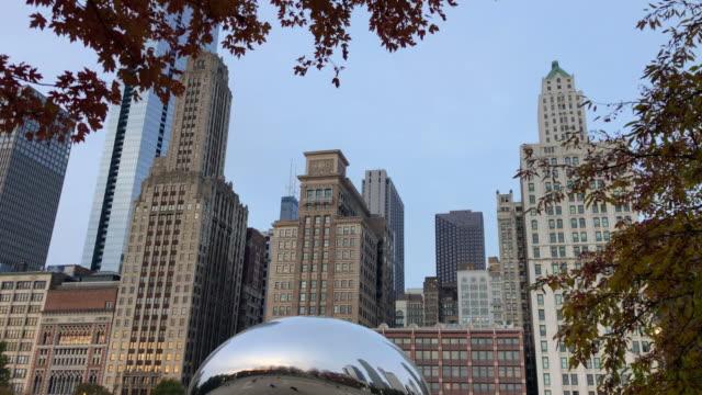 the cloud gate in the millennium park of chicago with autumn colors. - millennium park chicago bildbanksvideor och videomaterial från bakom kulisserna