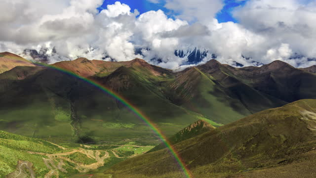 the clouds covered the snow mountain and suddenly a rainbow appeared - beauty in nature stock videos & royalty-free footage