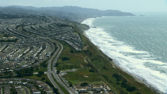 The coastal town of Daly City, located in the San Francisco Bay area. Neighborhoods on steep bluffs overlook Pacific Ocean waves.