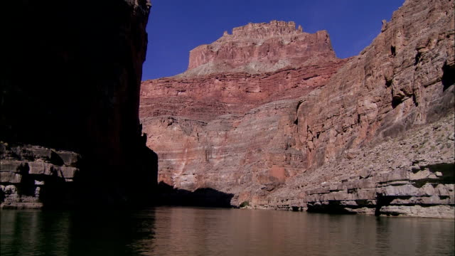 the colorado river approaches a gigantic butte in arizona's grand canyon. - butte rocky outcrop stock videos and b-roll footage