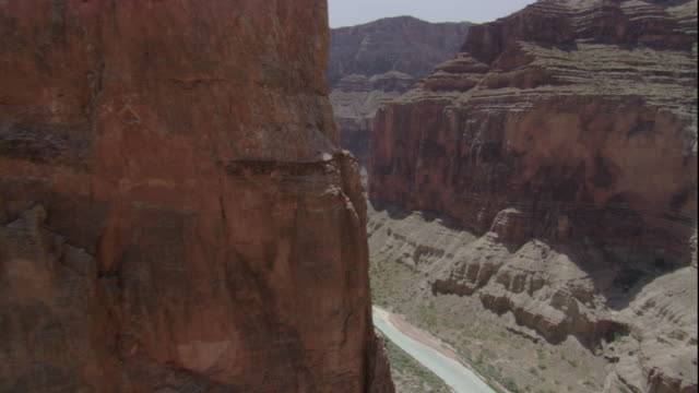 The Colorado River flows between the vertical cliffs of the Grand Canyon. Available in HD.