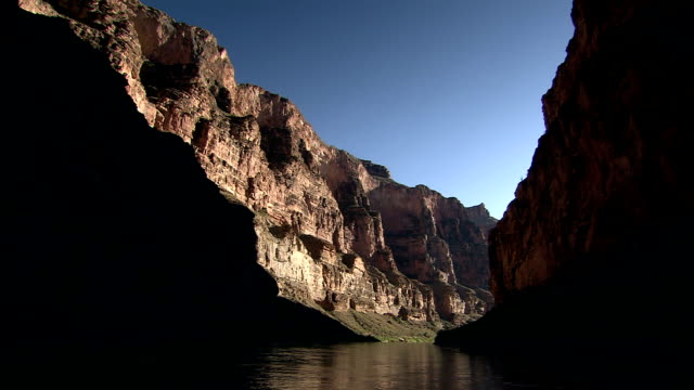 vidéos et rushes de the colorado river flows through a shadow-darkened grand canyon gorge. - colorado