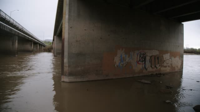 The Colorado River Flows Underneath Two Bridges with Graffiti