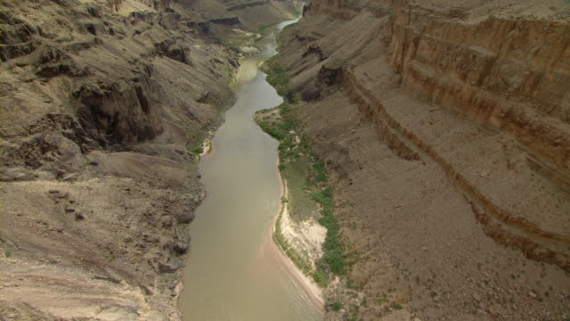 the colorado river winds through the rising cliffs of the grand canyon. - fluss colorado river stock-videos und b-roll-filmmaterial