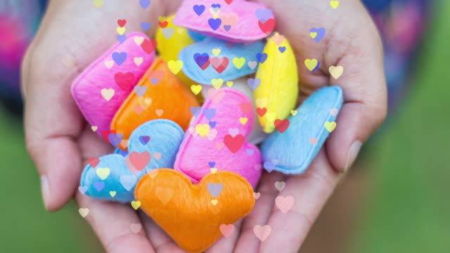 The colorful of heart shape in woman's hand with colorful heart motion graphic for valentine's day, Celebration of love