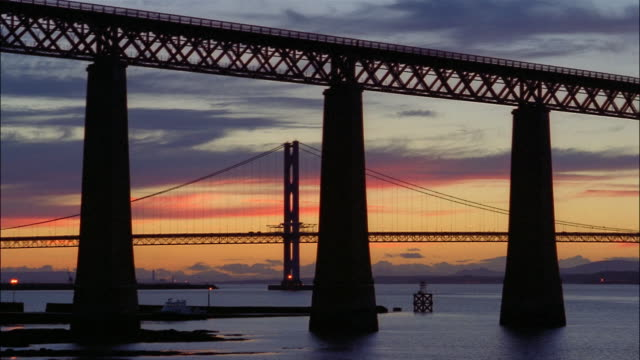 the colorful sky silhouettes forth road bridge and forth rail bridge in edinburgh, scotland. - fluss firth of forth stock-videos und b-roll-filmmaterial