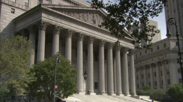 the columns are seen on the exterior of the new york supreme court building. - palazzo di giustizia video stock e b–roll